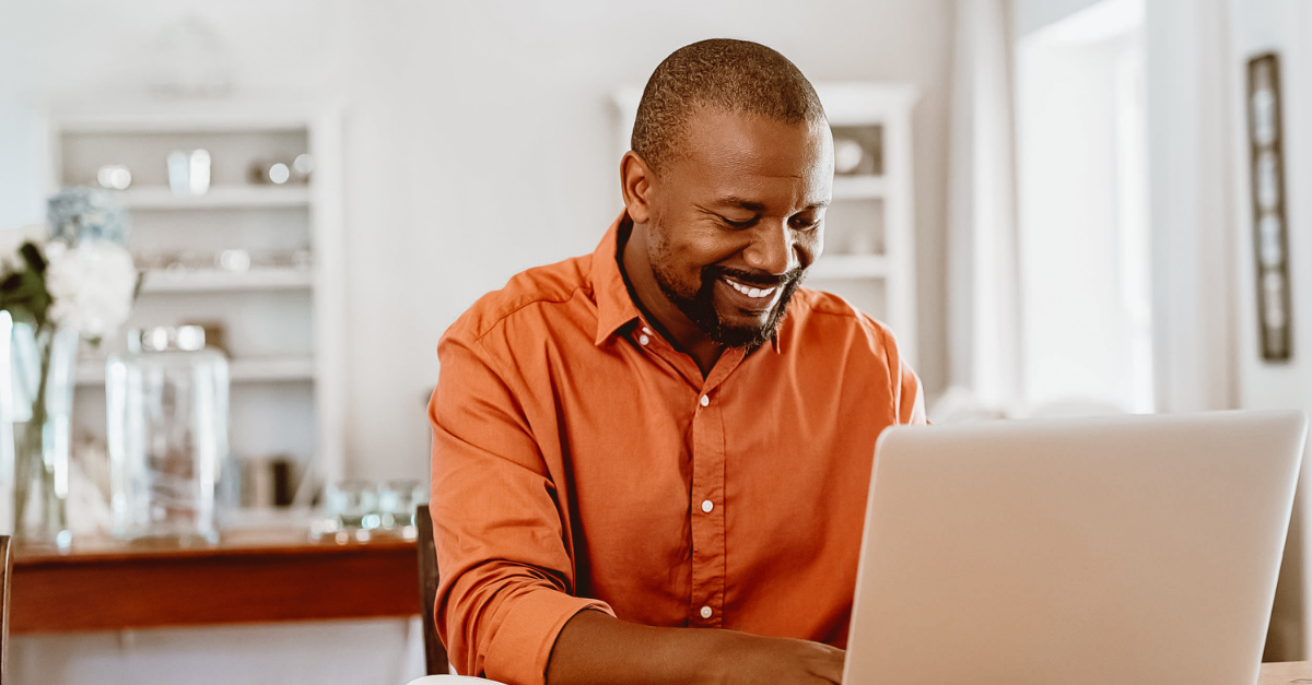 man in orange shirt working on home computer
