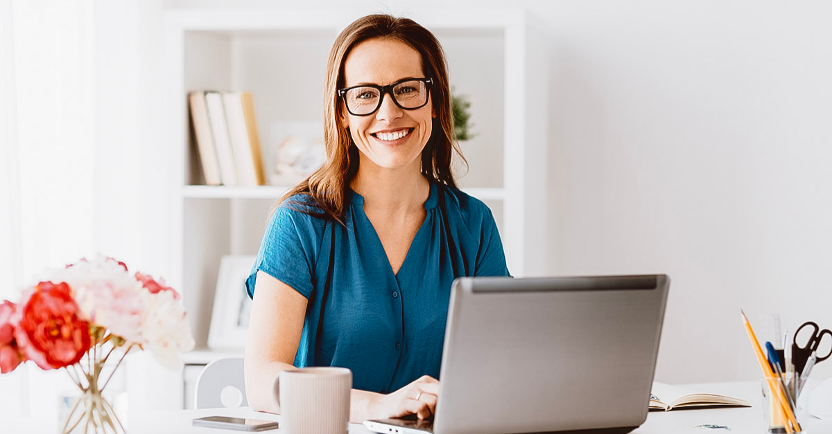 woman in blue shirt smiling at camera in home office